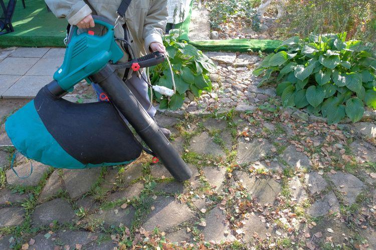 Práce s vysavačem listí v zahradě
