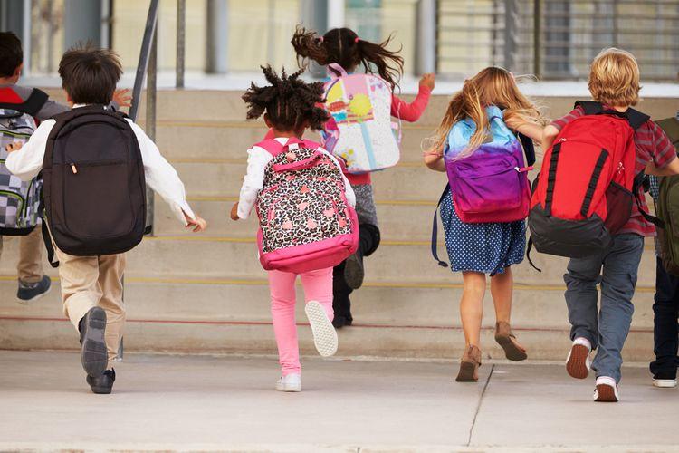 Děti utíkající do školy se školními batohy na zádech
