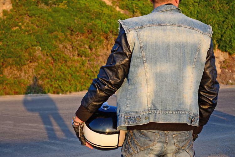 Motorkár v kožené bundě a riflové vestě
