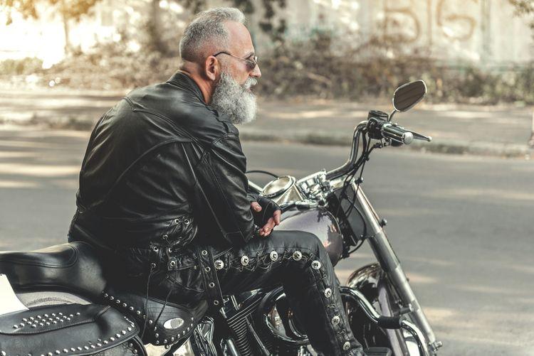Motorkář v kožených kalhotách a bundě