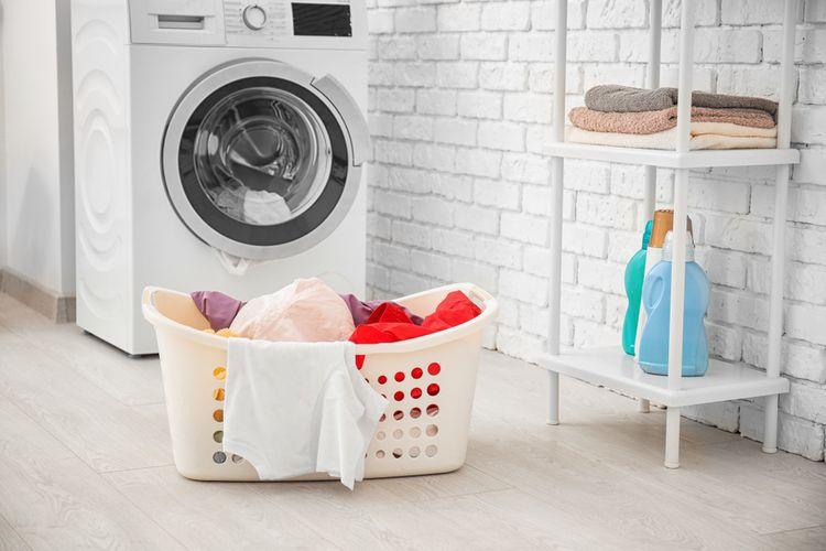 Zepředu plněná pračka a prádlo připravena na praní