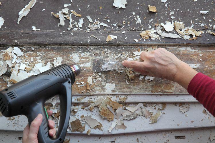 Odstraňování starého laku z okna pomocí horkovzdušné pistole