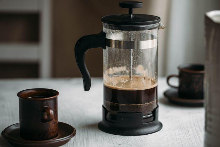 French press kávovar se šálky na stole