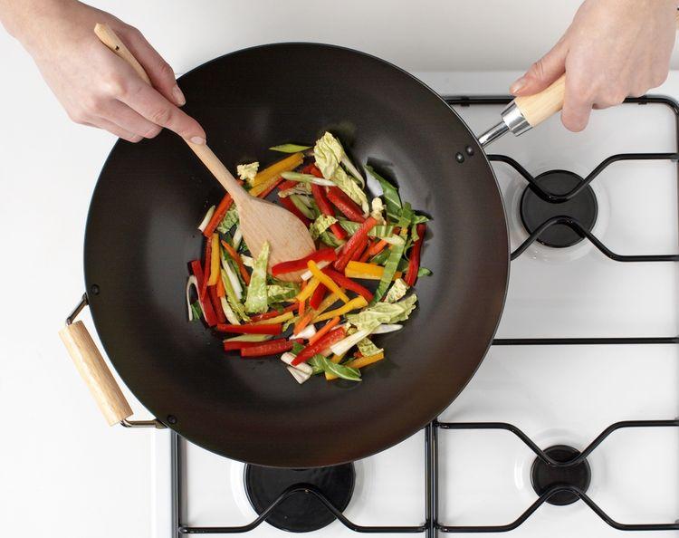 Příprava zeleniny v železné wok pánvi