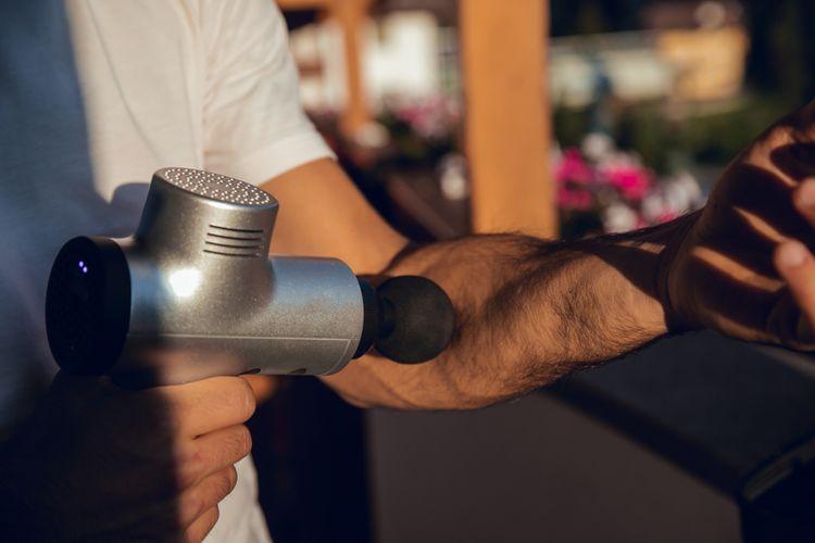 Masírování ruky masážní pistolí