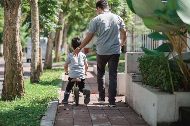 Dítě na odrážedle s otcem
