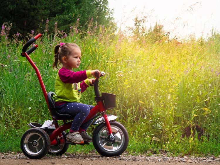 Červená šlapací tříkolka s rodičovskou vodící tyčí