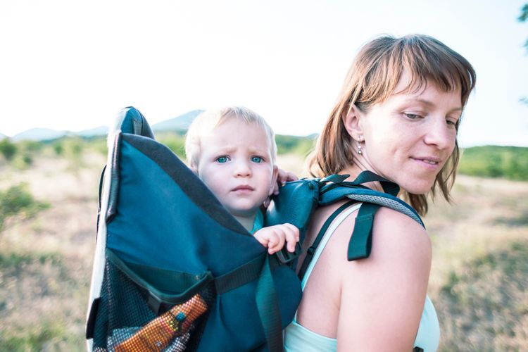 Dítě sedící v turistickém nosiči