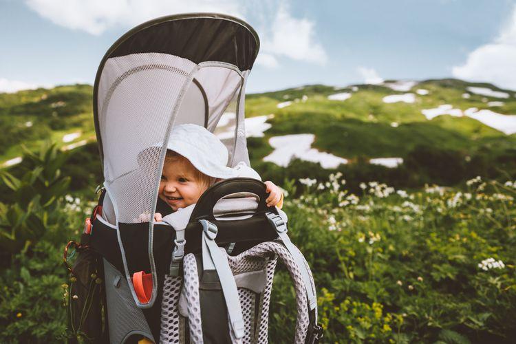 Dítě v turistickém nosiči se stříškou