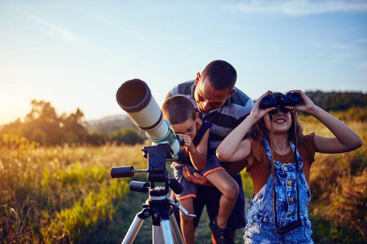 Rodina pozorující oblohu v přírodě pomocí teleskopu
