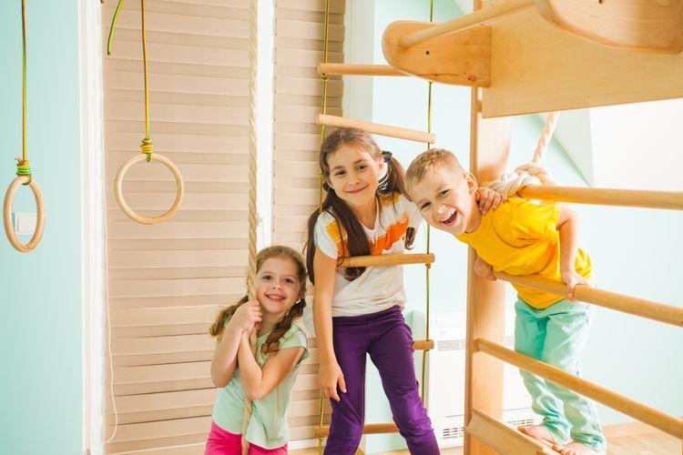 Děti cvičící na dřevěných žebřinách s příslušenstvím