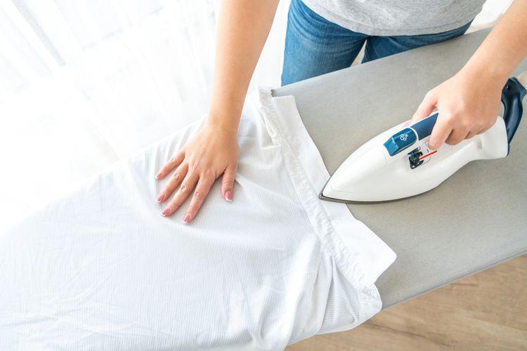 Žehlení bílé košile pomocí parní žehličky