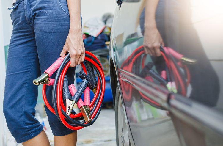 Žena se startovacími kabely při autě