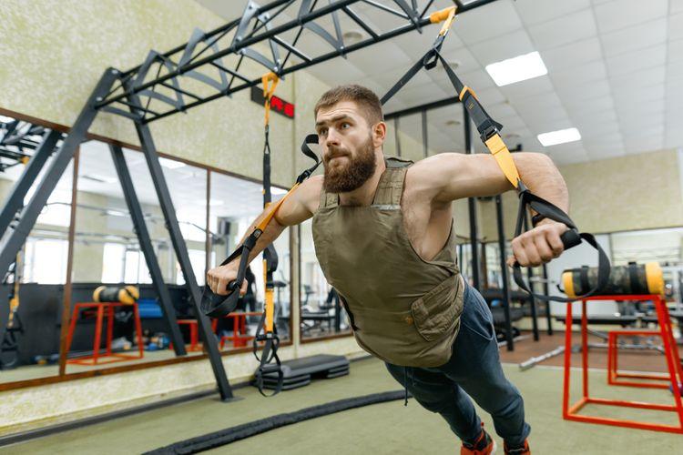 Trénink ve fitness centru se zátěžovou vestou